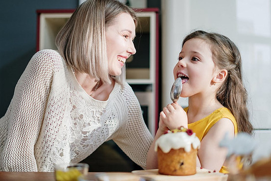 Mother looking at daughter eating her cake